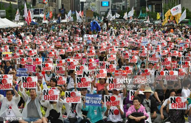 "South Korean protesters hold signs reading ""No Abe!"" during an anti-Japanese rally marking the anniversary of Korea's liberation from Japan's 1910-45..."