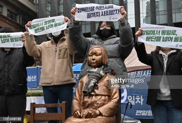 """South Korean protesters hold up banners beside a statue of a teenage girl symbolising """"comfort women"""", who served as sex slaves for Japanese soldiers..."""