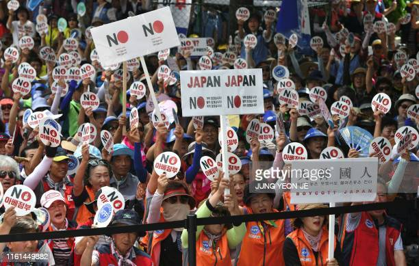 South Korean protesters hold up signs reading No Abe's government during an antiJapanese rally in central Seoul on August 13 2019 South Korea on...