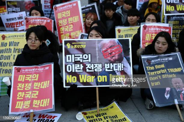 South Korean protesters holding signs take part in a protest against military conflict between the US and Iran in front of US embassy on January 18,...