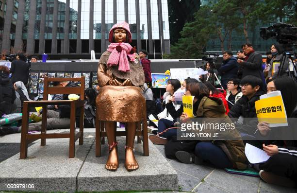 South Korean protesters sit near a statue of a teenage girl symbolizing former comfort women who served as sex slaves for Japanese soldiers during...