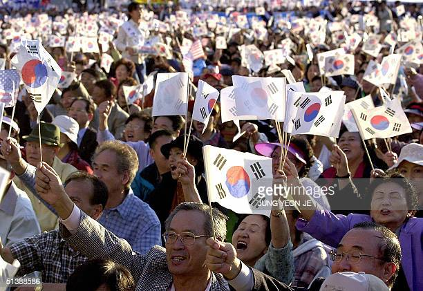 South Korean protesters wave US and South Korean national flags during an antiNorth Korea rally in front of the city hall in Seoul 04 October 2004...