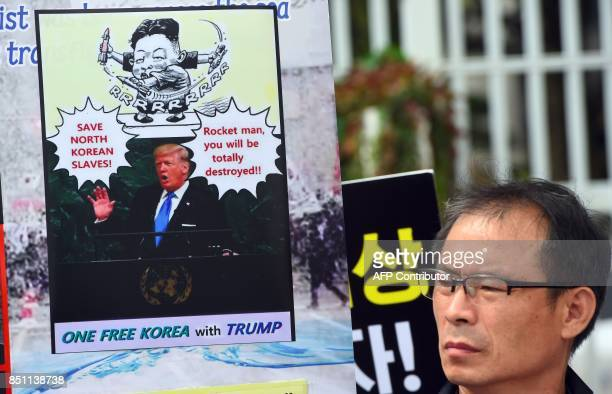 A South Korean protestor holds a placard showing a picture of US President Donald Trump during an antiNorth Korea rally outside South Korean...