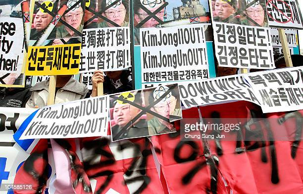 South Korean protestors hold portraits of North Korean leader Kim JongIl and his son Kim JongUn and shout slogans at a rally opposing recent...