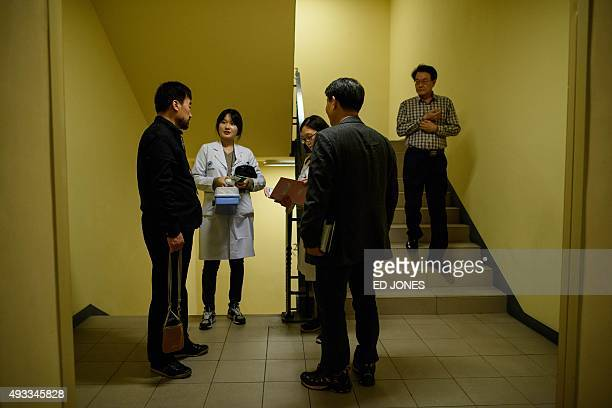 South Korean Red Cross medics talk with people selected to attend a family reunion in North Korea at a hotel used as a gathering point in Sokcho on...