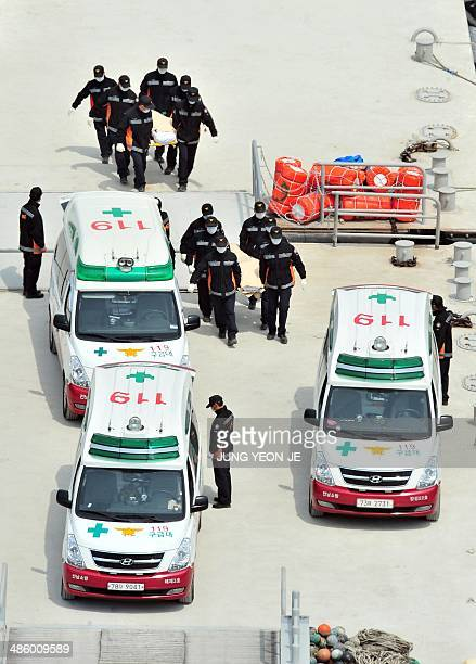 South Korean rescue members carry the bodies of victims recovered from the 'Sewol' ferry to ambulances at a harbour in Jindo on April 22 2014 The...