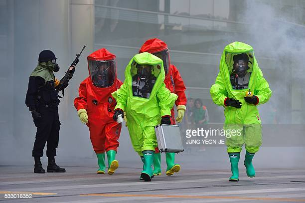 South Korean rescue members wearing chemical protective suits participate in an antiterror drill as part of a disaster management exercise at the...