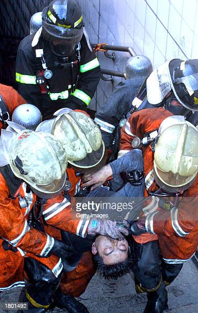 South Korean rescue team members administer first aid to a survivor of a subway fire at the entrance of a subway station February 18, 2003 in Daegu,...