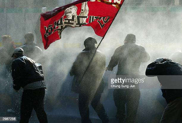 South Korean riot police direct a water cannon at protesters during an anti-government rally against the controversial bill on the free trade...