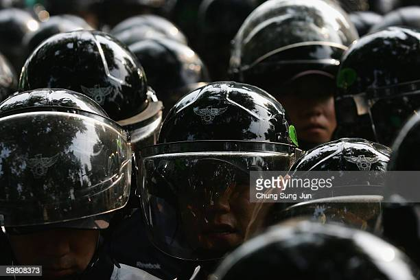 South Korean riot police stand in front of protestors during the commemorate Korea's 64th Independence Day on August 15 2009 in Seoul South Korea...