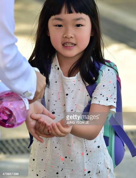 A South Korean school student uses hand sanitizer to protect against possible MERS virus at an elementary school in Seoul on June 3 2015 South Korea...