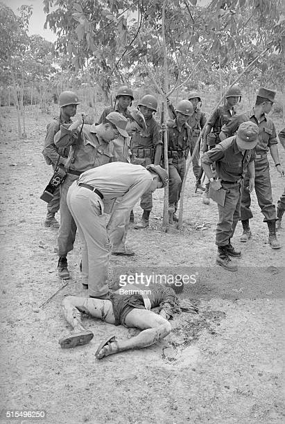 South Korean security troops look at the body of a Viet Cong guerrilla who was killed following heavy communist mortar attacks on a Korean engineers'...