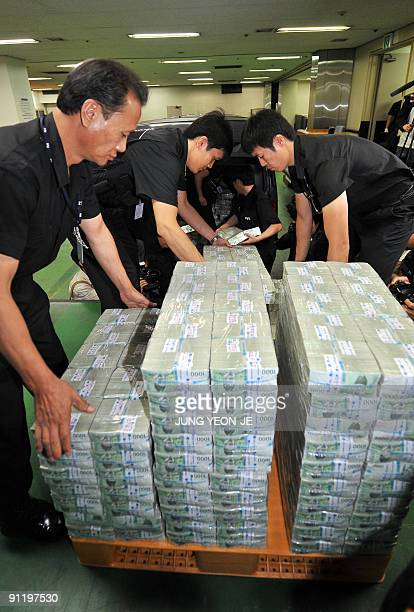 South Korean security workers prepare a batch of new money for release in the basement of the central bank in Seoul on September 28 2009 The release...