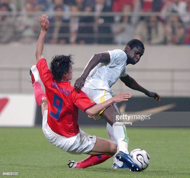 South Korean soccer player Ahn Jung Hwan left falls down in a fight for the ball with a Senegal soccer player during a friendly match at the Seoul...