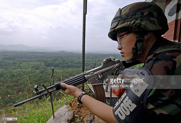 South Korean soldier aims a K2 assault rifle from an observation point on the southern side of the demilitarized zone Paju 07 July 2006 South Korea...