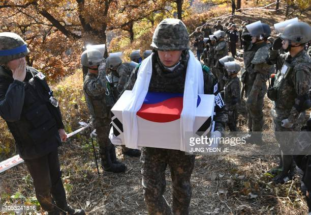 South Korean soldier carries a coffin containing a piece of bone believed to be the remains of an unidentified South Korean soldier killed in the...
