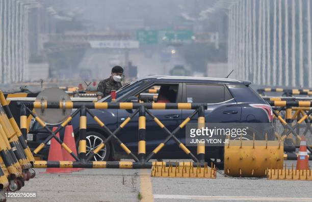 South Korean soldier checks a car at a checkpoint on the Tongil bridge, the road leading to North Korea's Kaesong joint industrial complex, near the...