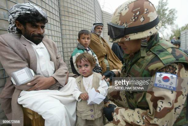 A South Korean soldier checks an Iraqi girl with face burns before sending her for check up 02 December 2003 at the Korean hospital in the US...