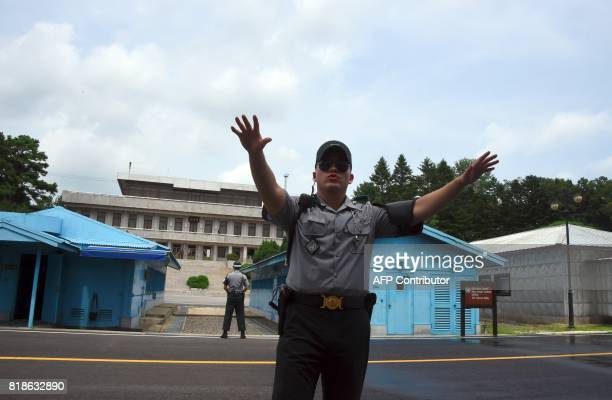 A South Korean soldier gestures to cameramen during a press tour to the truce village of Panmunjom in the Demilitarized Zone dividing the two Koreas...