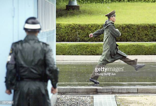 South Korean soldier looks at a North Korean soldier as he marches past at the truce village of Panmunjom in the demilitarized zone between South and...