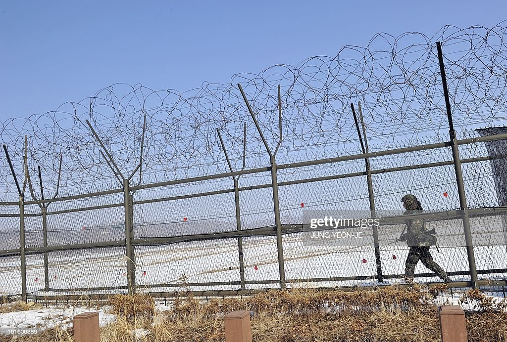 A South Korean soldier patrols along a military iron fence in Paju near the demilitarized zone dividing the two Koreas on February 13, 2013. South Korea said on February 13 it would accelerate the development of longer-range ballistic missiles that could cover the whole of North Korea in response to a third nuclear test by Pyongyang.