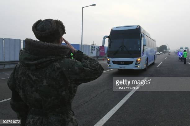 A South Korean soldier salutes as a bus transporting a South Korean delegation for interKorea workinglevel talks passes a military checkpoint leading...