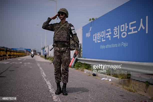 A South Korean soldier salutes as he stands on the Unification Bridge that leads to the Demilitarized Zone between North and South Korea in Paju on...