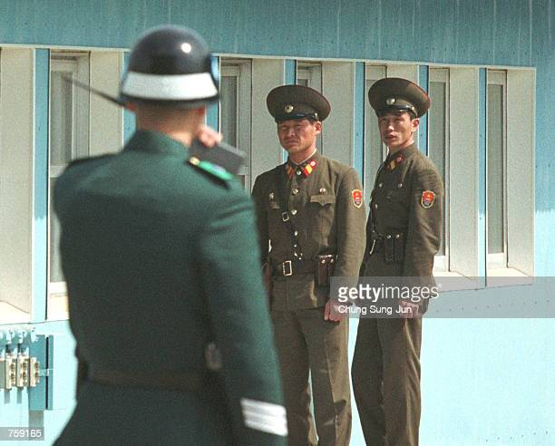 South Korean soldier speaks into a walkietalkie as North Korean military officers stand guard at the truce village of Panmunjom April 10 2002 north...