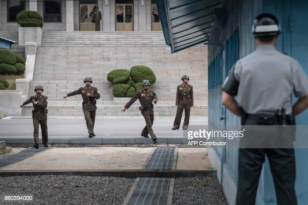 A South Korean soldier stands before North Korean soldiers walking towards the military demarcation line separating North and South Korea at the...