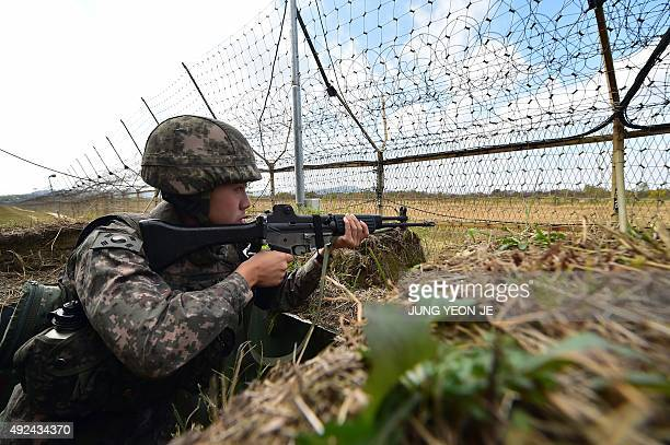 A South Korean soldier stands guard in front of a military fence at a General Outpost of the Demilitarized Zone dividing the two Koreas in Cheorwon...