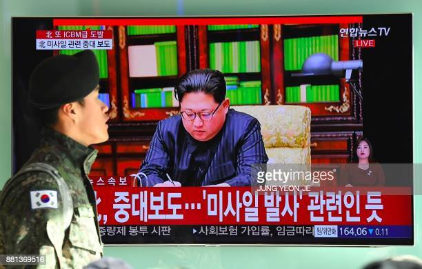 A South Korean soldier walks past a television news screen showing North Korean leader Kim JongUn approving the country's new ICBM test at a railway...