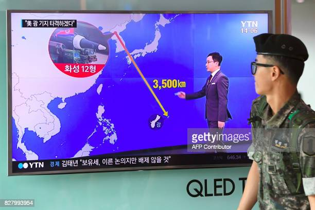 South Korean soldier walks past a television screen showing a graphic of the distance between North Korea and Guam at a railway station in Seoul on...