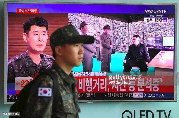 A South Korean soldier walks past a television screen showing file footage of North Korean leader Kim JongUn at a railway station in Seoul on July 4...
