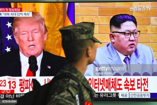 South Korean soldier walks past a television screen showing pictures of US President Donald Trump and North Korean leader Kim Jong Un at a railway...