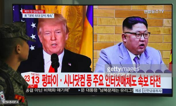 A South Korean soldier walks past a television screen showing pictures of US President Donald Trump and North Korean leader Kim Jong Un at a railway...