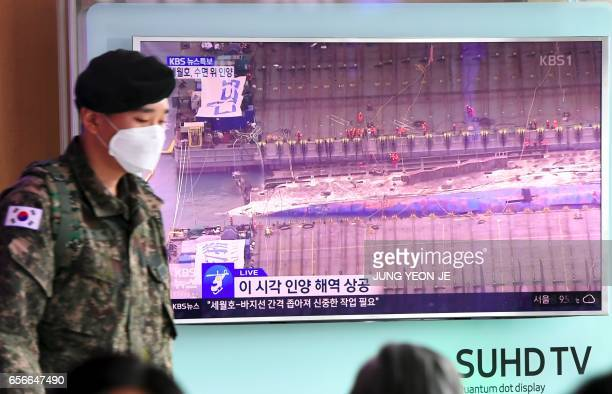 A South Korean soldier walks past a television screen showing the damaged Sewol ferry between two barges during a salvage operation at a railway...