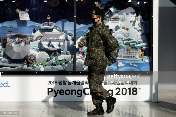 South Korean soldier walks past the 2018 PyeongChang Winter Olympic and Paralympic Games PR booth on January 5 2018 in Seoul South Korea North Korea...