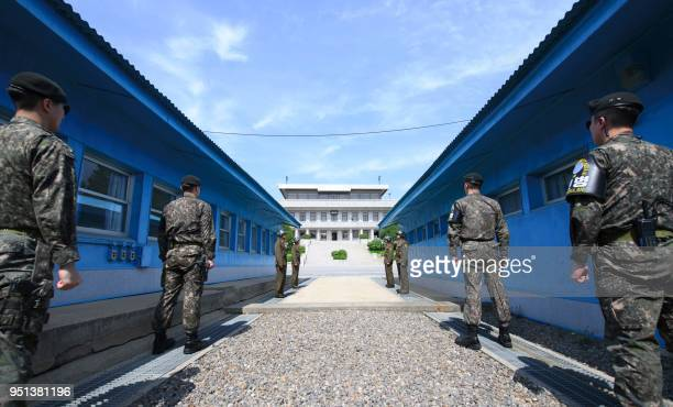 TOPSHOT South Korean soldiers and North Korean soldiers stand guard before the military demarcation line on the each side of the truce village of...