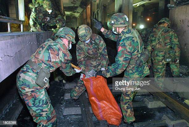 South Korean soldiers bag debris in a subway station destroyed by fire February 19, 2003 in Daegu, South Korea. Kim Dae-han, a 56-year-old man with a...