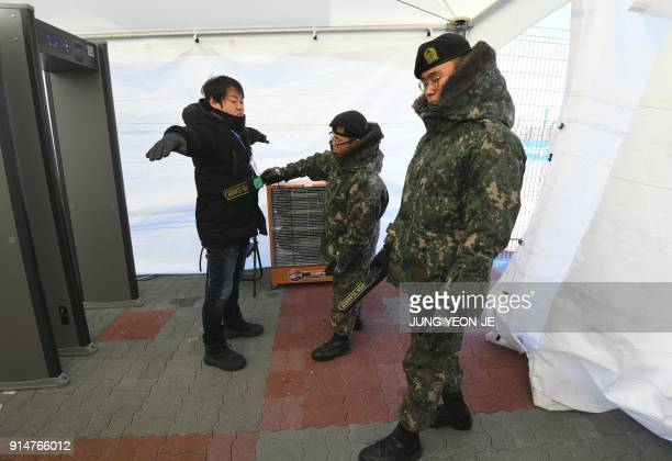South Korean soldiers inspect a visitor at a security checkpoint as they replace security guards showing symptoms of the norovirus at the Gangneung...