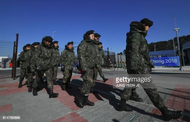 South Korean soldiers move at a security checkpoint as they replace security guards showing symptoms of the norovirus at the Gangneung Ice Arena in...