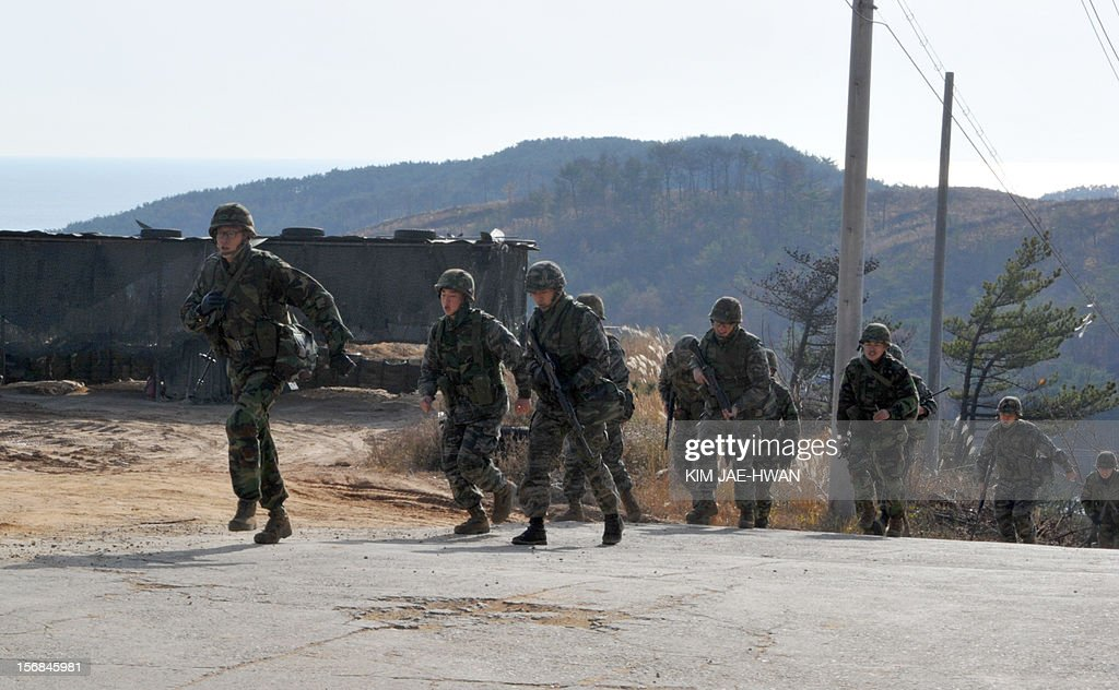 South Korean soldiers run during an exercise to mark the second anniversary of North Korea's shelling on Yeonpyeong Island on November 23, 2012. The November 23, 2010 attack on Yeonpyeong island killed two South Korean marines and two civilians in one of the most serious border incidents since the 1950-1953 Korean War.