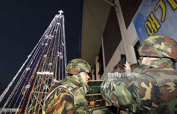 South Korean soldiers stand guard as Christians stage a lighting ceremony in front of a Christmas tree atop a militarycontrolled hill near the tense...