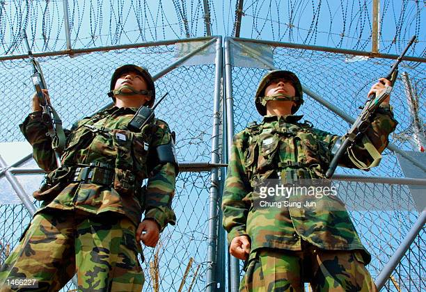 South Korean soldiers stand guard as their colleagues work to reconnect the interKorean railway October 9 2002 in the Demilitarized Zone in Paju...