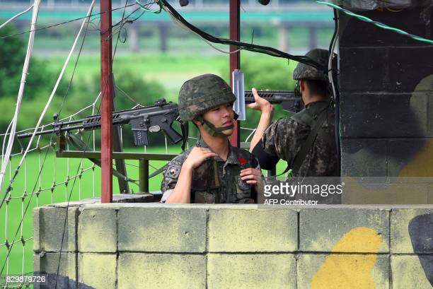 South Korean soldiers stand guard at a guard post near the Demilitarized Zone dividing two Koreas in the border city of Paju on August 11 2017 As...