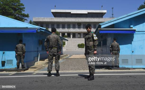 TOPSHOT South Korean soldiers stand guard before the military demarcation line during a press tour to the border truce village of Panmunjom in the...