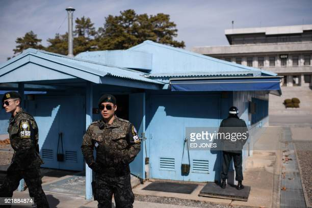 South Korean soldiers stand guard before the military demarcation line and North Korea's Panmun Hall in the truce village of Panmunjom within the...