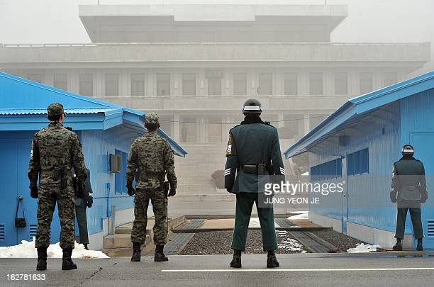 South Korean soldiers stand guard in fog as a North Korean soldier is seen at the truce village of Panmunjom in the demilitarized zone dividing North...