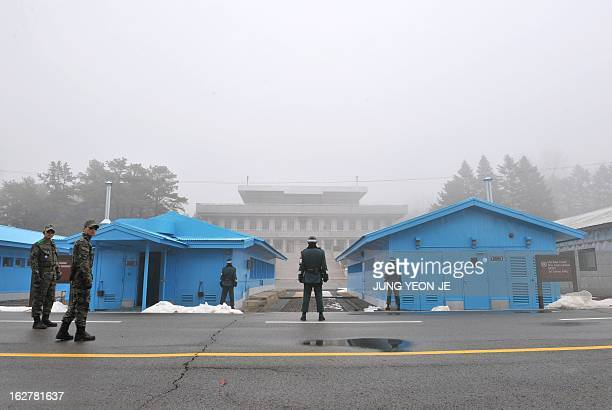 South Korean soldiers stand guard in fog at the truce village of Panmunjom in the demilitarized zone dividing North and South Korea on February 27...