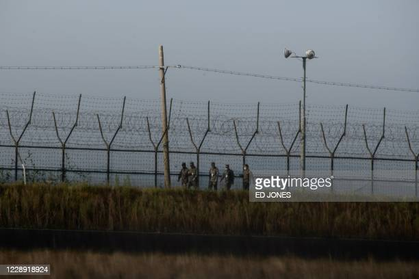 South Korean soldiers walk along a fence of the Demilitarized Zone separating North and South Korea, on the South Korean island of Gyodong on October...